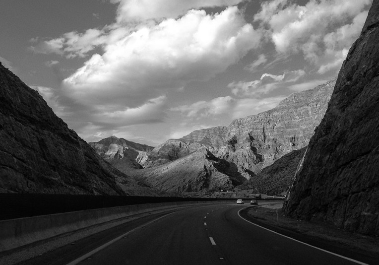 Black and white photo of a highway going through a mountain pass in the southwest